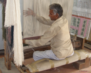 Man sits at loom and weaves